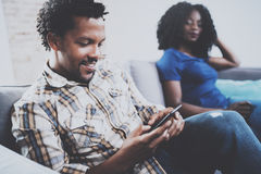 Smiling african american couple relaxing together on the sofa.Young black man using smartphones while rest at home in Stock Photography