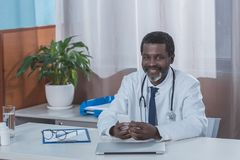 Smiling african american doctor sitting at the table. And holding smartphone Stock Photo