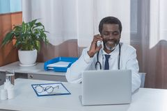 Smiling african american doctor sitting at the table and talking. By smartphone Stock Photos