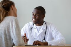 Free Smiling African American Doctor Talking To Patient At Visit Stock Photos - 174101533