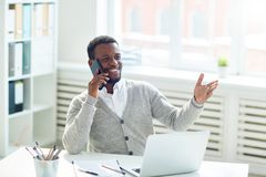 Conducting Telephone Negotiations. Smiling African American entrepreneur sitting at office desk and conducting telephone negotiations with business partner Royalty Free Stock Photo