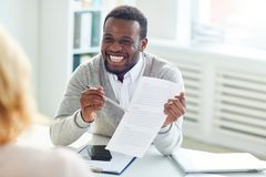 Discussing Cooperation with Business Partner. Smiling African American entrepreneur sitting at office desk and discussing details of mutually beneficial stock photos