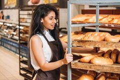 Smiling african american female shop assistant in apron arranging fresh pastry. In grocery store royalty free stock photo