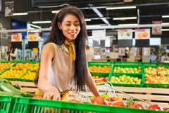 Smiling african american female shopper choosing food. In grocery store stock images