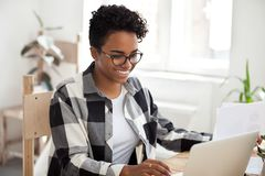Smiling African American female work with laptop and papers stock photo