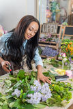 Smiling african american florist holding secateurs and working with flowers Stock Images