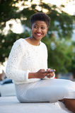 Smiling african american girl sitting outside with cell phone Royalty Free Stock Image