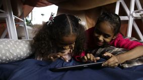 Smiling african american girls using tablet pc. Smiling cute african american sisters scrolling pages on digital tablet while lying on the floor in cubby house stock video footage