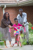 Smiling African American Grand Parents Helping Little Girl Bikin Stock Photography