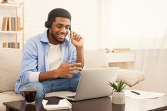 Smiling african-american guy in headphones looking at laptop stock photography