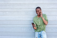 Smiling african american guy listening to music with earphones. Portrait of a smiling african american guy listening to music with earphones Stock Images