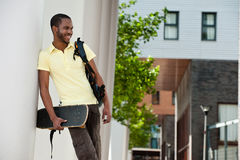 Smiling African American Guy with Skateboard Royalty Free Stock Images