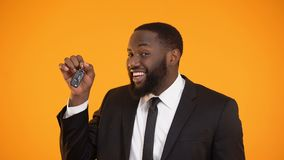 Smiling african-american male showing automobile keys, renting car, leasing. Stock footage stock video footage