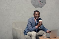 Smiling african american man in blue jacket with coffee. And laptop stock photo