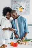 Smiling african american man cooking breakfast and using smartphone together with wife in kitchen. At home stock photo