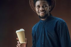 Smiling african american man with disposable coffee cup. Isolated on brown Stock Photo