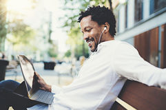 Smiling African American man in headphones making video conversation outside on electronic touch pad,checking e-mail Stock Photography