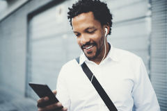 Smiling African American man in headphones standidng in sunny street listening to songs on his cell phone, using Stock Image