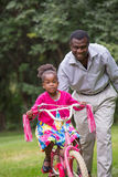 Smiling African American Man Helping Little Girl Biking Stock Photography
