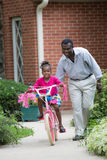 Smiling African American Man Helping Little Girl Biking Stock Photo