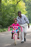 Smiling African American Man Helping Little Girl Biking Stock Photos