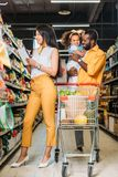 smiling african american man holding daughter while his wife choosing food with shopping list royalty free stock image