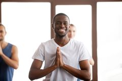 Smiling african-american man holding hands in namaste at group t. Smiling african-american men holding hands in namaste gesture, happy black positive guy ready royalty free stock photos