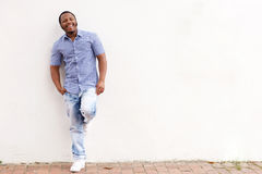 Smiling african american man leaning against white wall Royalty Free Stock Photo
