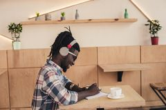 smiling african american man listening music and writing in notepad in coffee royalty free stock photography