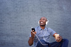 Smiling african american man listening to music on headphones Stock Photos