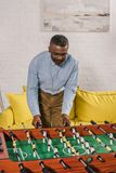 Smiling african american man playing table football. At home stock photos