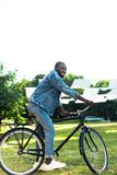 Smiling african american man riding retro bicycle. In park royalty free stock images