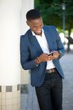 Smiling african american man sending text message Stock Photography