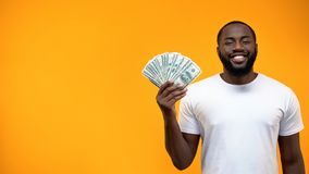 Smiling African-American man showing bunch of dollars, template for text, ad