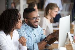 Smiling African American man showing funny news to colleague. Smiling happy African American men showing funny news to female colleague, looking at screen stock photo