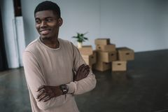 Smiling african american man standing with crossed arms and looking away in new office. During relocation stock photos