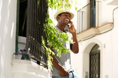 Smiling african american man talking on mobile phone outside Royalty Free Stock Images
