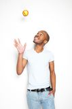 Smiling african american man throwing an apple in the air Royalty Free Stock Image