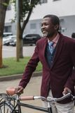 Smiling african american man in trendy burgundy jacket with bicycle. In city stock photography