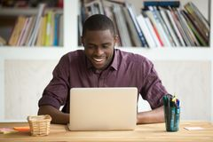Smiling african-american man using laptop sitting at home office. Desk, happy excited black e business owner looking at computer screen pleased by reading good Royalty Free Stock Photos