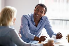 Smiling african american manager talking with client at business meeting. Smiling african american professional manager advisor designer talking with client stock photography