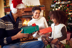 Smiling African American parent give Christmas present their lit Royalty Free Stock Photography