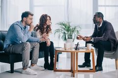 Smiling african american psychiatrist talking to young couple. In office Stock Photo