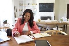Smiling African American  retired woman sitting at a table writing in her dining room, close up stock photography