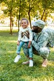 smiling african american soldier in military uniform holding happy daughter royalty free stock photography