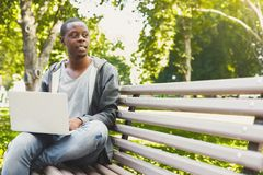 A smiling african-american student with laptop outdoors. Handsome smiling african-american student in a pleasant atmosphere outdoors, in university campus Stock Photos