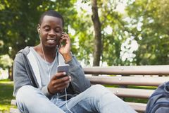 Smiling african-american student listening to music outdoors. Smiling african-american student listening to music on his smartphone outdoors, having a rest in Royalty Free Stock Images