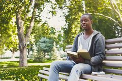 African-american student reading a book outdoors. Smiling african-american student reading a book in the park, studying and preparing for exams at the university Stock Image