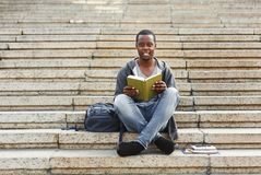 Smiling african-american student reading book on university stairs. Preparing for exams at college or university. Education concept, copy space Royalty Free Stock Photo