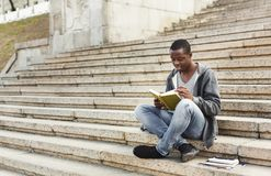 Smiling african-american student reading book on university stairs. Preparing for exams in university campus. Education concept, copy space Royalty Free Stock Images